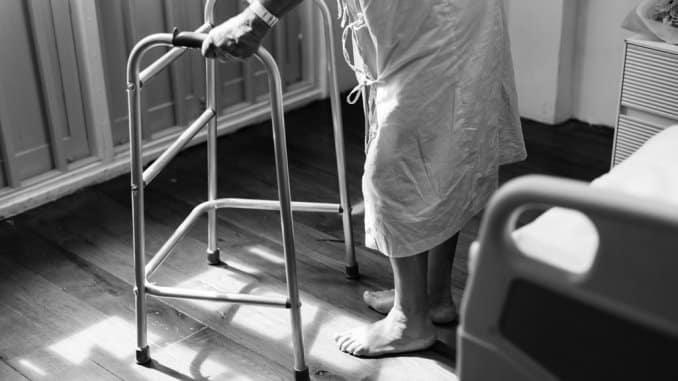 Crno bijela slika osobe oboljele od multiple skleroze s hodalicom.