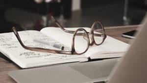 Naočale, bilježnica i laptop na radnom stolu