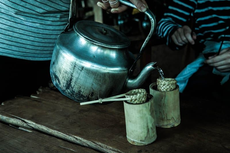 Točenje čaja iz velikog starinskog čajnika u drvene šalice.