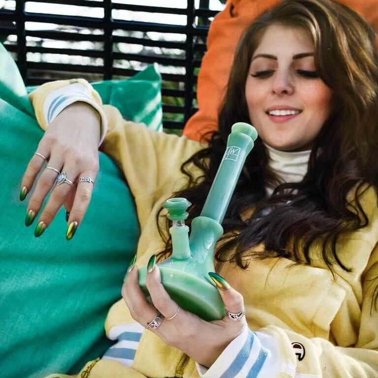Djevojka puši bong na fotelji