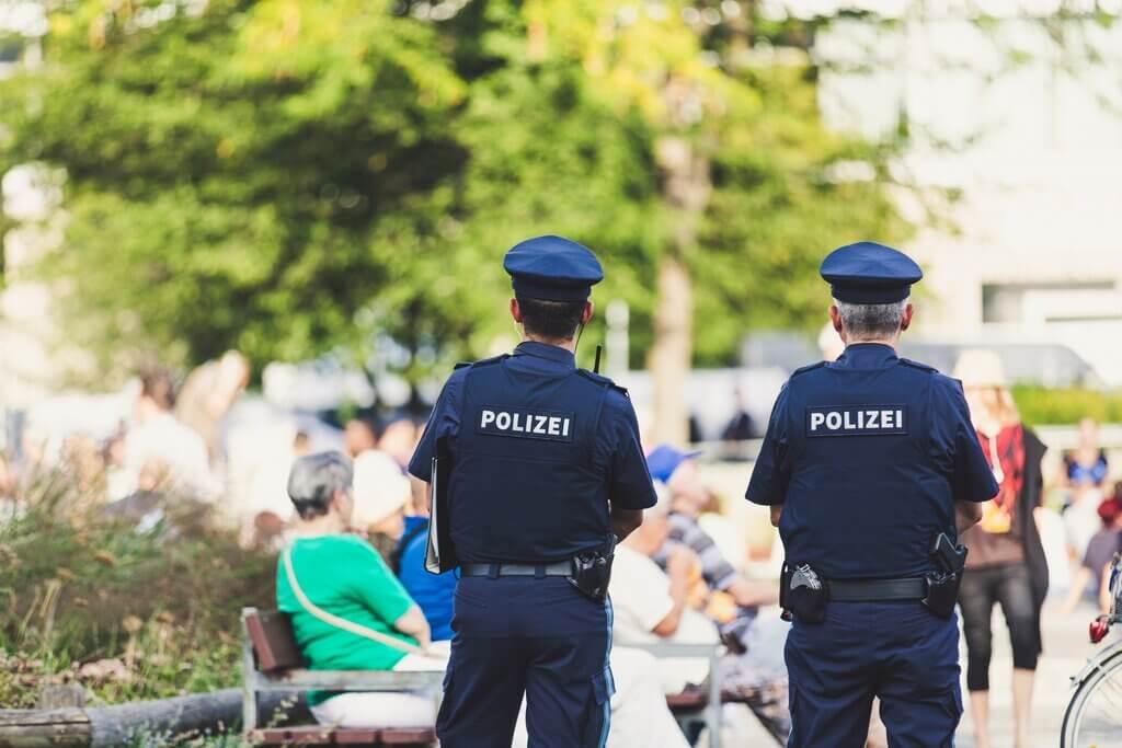 Dva policajca u Njemačkoj, leđima okrenuti, stoje na ulici.