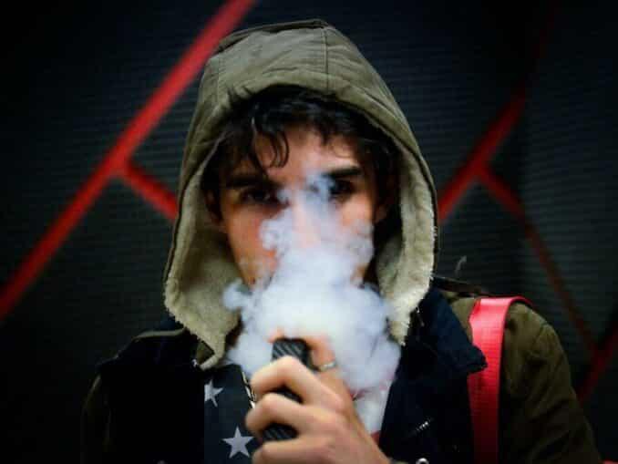 Čovjek s kapuljačom puši e-cigaretu s CBD e-tekućinom.